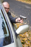 Man with gun. Danger gangster traveling by car stock image