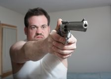 Man With Gun. Man in home aiming gun ready to fire focus on hands Royalty Free Stock Images