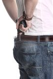 Man with gun behind back. Closeup of a man pulling a gun or pistol from the back of his pants.  White background Royalty Free Stock Photo