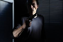 Man with gun  on black door window, policeman, detective, bodyguard and self defense concept, otherwise robber, murderer. And thief concept royalty free stock photo