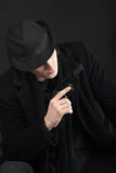 Man with gun and black hat Stock Photo