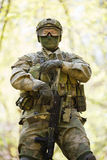Man with gun and camouflage. Stands in summer forest Royalty Free Stock Photography