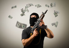 Man with gun and dollar banknotes. Royalty Free Stock Images