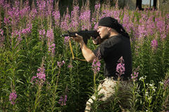 Man with gun. Among flowers stock photography