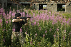 Man with gun. Among flowers royalty free stock image