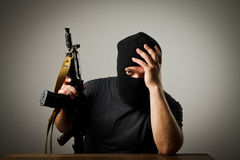 Man with gun. Frustrated man wearing balaclava with a gun. Headache concept stock images