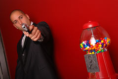 Man, gun and gumball machine. Man pointing a gun at the camera, there is a gumball machine to the right Royalty Free Stock Images
