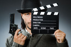 Man with gun and movie. Clapboard Royalty Free Stock Photography