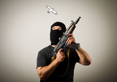 Man with gun and peace dove. Stock Image