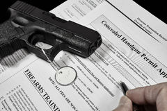 Man with gun and permit application documents Stock Photos