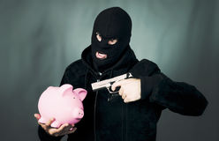 Man with a gun and piggy bank Royalty Free Stock Images