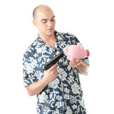 Man with gun pointing at piggy bank Stock Images