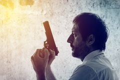 Man with a gun. Police officer, criminal investigation detective or secret service agent. Grunge edit Royalty Free Stock Photography
