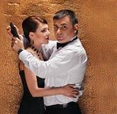 Man with gun protecting his woman Stock Photos