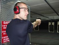 Man at gun range. Getting ready to shoot at a target, wearing eye and ear protection Royalty Free Stock Photo