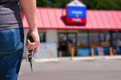 Man with gun ready to rob a convenience store. A criminal man is standing with his gun in his hand outside of a convenience store which he is about to rob Stock Photography