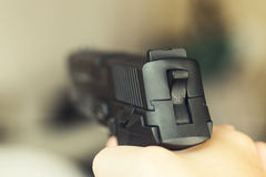 Man with a gun ready to shoot - focus on the back part of gun Stock Photo