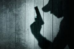 Man with a gun in shadow on a wooden background Stock Photography