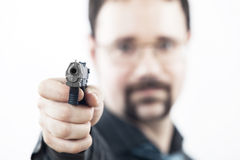 Man with a gun shooting. In our direction Royalty Free Stock Images
