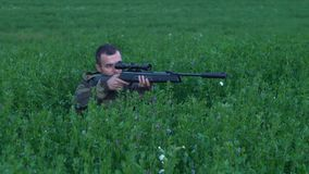 Man with a gun sitting in the tall grass 4k