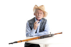 Man with a gun smokes a cigarette. Elderly man in a hat sitting at a table with a gun and smokes a cigarette on a white background Royalty Free Stock Images