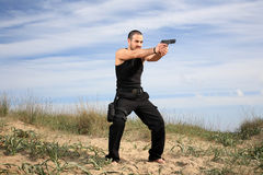 Man with gun. Special forces man at the beach holding a gun Stock Photography