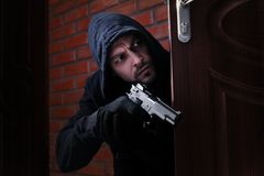 Man with gun spying behind open door. Criminal offence. Man with gun spying behind open door indoors. Criminal offence stock photography