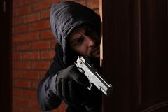 Man with gun spying behind open door. Criminal offence. Man with gun spying behind open door indoors. Criminal offence royalty free stock image