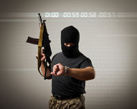 Man with gun. Terrorist with gun looking at his wristwatch. Time concept stock photo