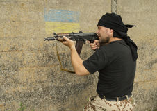 Man with gun. Man wearing black scarf with a gun. Flag of Ukraine on the wall stock photos