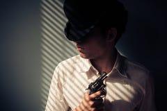 Man with gun by window Stock Photos