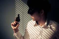 Man with gun by window Royalty Free Stock Images