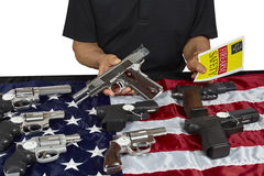 Man with guns For Sale with Safety Brochure on American USA Flag Royalty Free Stock Photography