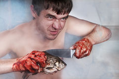 Man guts fish. Man in the kitchen with a large knife fish cleaners. his hands in the blood royalty free stock photos