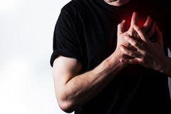 Man, guy in a black t shirt on a white background hold hands on his heart, heart atack, severe heartache, chest  myocardial infarc Royalty Free Stock Photos