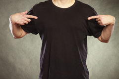 Man guy in blank shirt with copy space pointing. Fashionable casual man in black blank shirt with empty copy space pointing at himself. Guy in studio on black stock photo