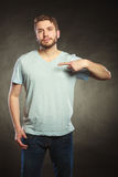 Man guy in blank shirt with copy space pointing. Stock Image