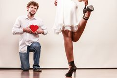 Man with heart shaped gift box for woman. Man guy holding heart shaped present gift box for hot women girl in high heels. Valentine day love concept stock images