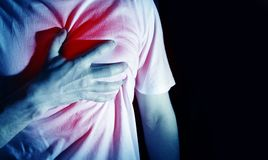 Man, guy in a white t shirt on a black background in a blue color hold hands on his heart, heart atack, severe heartache, chest m. Yocardial royalty free stock photos