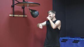 The man in the gym. Athletic man pounding a punching bag in a sports club stock video footage
