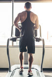 Man at the gym. Back view of handsome muscular man running on a treadmill in gym Stock Photos
