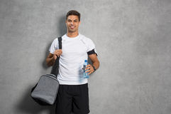 Man with gym bag. Portrait of young man athlete with bag and bottle of water. Fitness guy isolated over grey background looking at camera. Latin man listening to Stock Photos