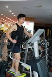 Asian chinese man in gym doing cardiovascular exercise. Man in gym doing cardiovascular exercise on a crosstrainer in a gym Stock Photo