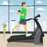 Man at gym doing exercise on the treadmill with smartphone armband drinking water. Man at the gym doing exercise on the treadmill with smartphone armband Royalty Free Stock Photo