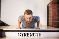 Man In Gym Doing Press-Ups On Step Labeled Strength Stock Photography