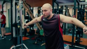Man in gym doing pulls weight on cable machine. Man in gym doing pulls weight exercise 4k video. Male bodybuilder training chest muscles exercise using cable stock video