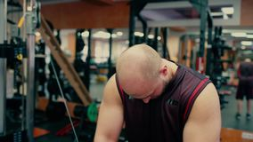 Man in gym doing pulls weight on cable machine. Man in gym doing pulls weight exercise 4k video. Male bodybuilder training chest muscles exercise using cable stock footage