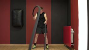 The man in the gym is engaged in cross fit. A man pulls a rope for functional trening stock footage