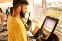 Man at the gym exercise on bike and surfing on Internet Stock Image
