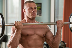 Man In The Gym Exercising Biceps With Barbell Royalty Free Stock Photos